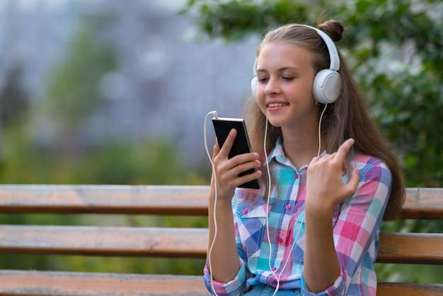 Молодая женщина сидит на скамейке в парке, слушает музыку на своем мобильном телефоне в наушниках, глядя на экран с улыбкой удовольствия