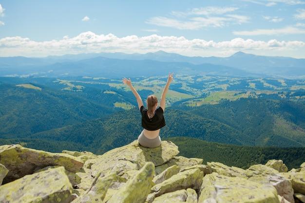 Молодая женщина сидит на скале и смотрит на горизонт.