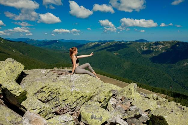 Молодая женщина сидит на скале и смотрит на горизонт