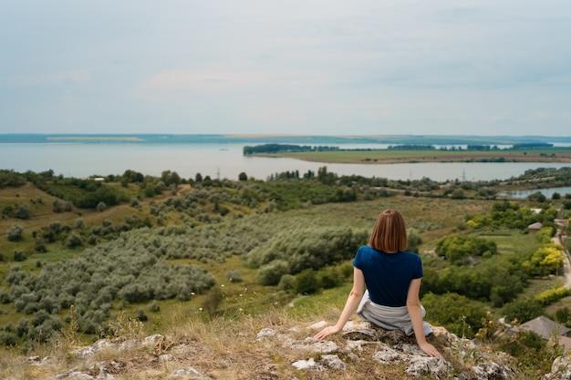 平和な瞬間を楽しんでいる岩の上に座っている若い女性。