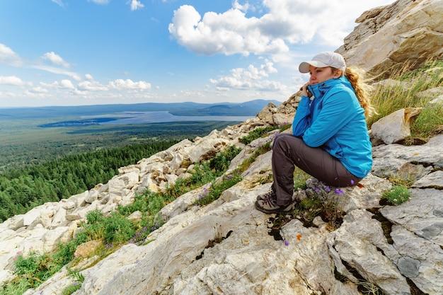 山の岩の上に座って地平線を見ている若い女性