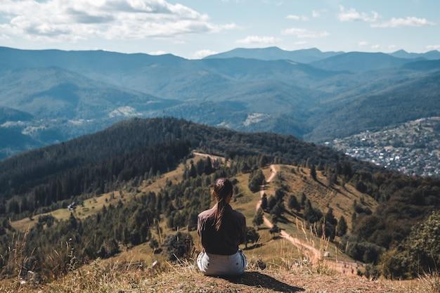 バックパックと岩の上に座って、地平線を見ている若い女性