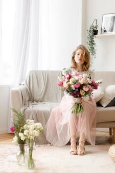 Молодая женщина, сидя на диване с букетом цветов