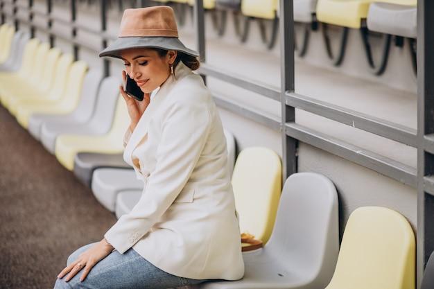 Молодая женщина сидит на местах арены и разговаривает по телефону