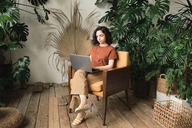안락의자에 앉아 나무 바닥과 녹색 식물이 있는 방에서 노트북을 사용하여 온라인으로 일하는 젊은 여성