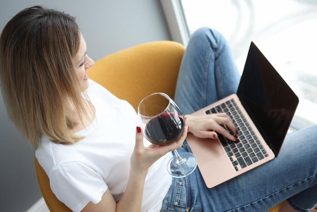 노트북과 안락의 자에 앉아 유리에서 레드 와인을 마시는 젊은 여자