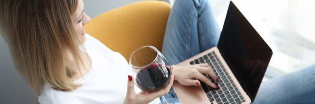 Молодая женщина сидит в кресле с ноутбуком и пьет красное вино из стекла