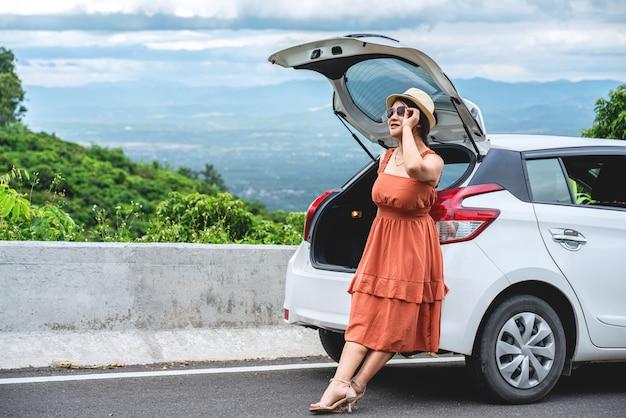 Молодая женщина, сидящая на задней части автомобиля и смотрящая на прекрасный вид