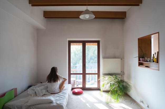 Молодая женщина сидит на кровати и смотрит в окно.