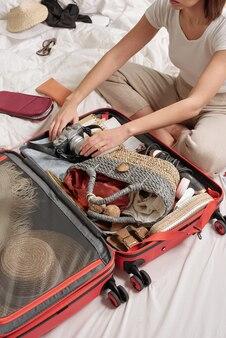 ベッドに座って写真カメラを荷物に詰める若い女性