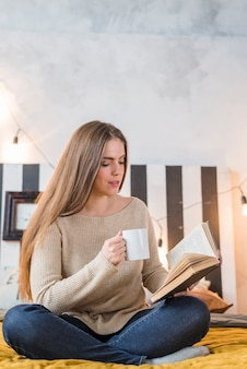 Young woman sitting on bed holding coffee cup in hand reading book