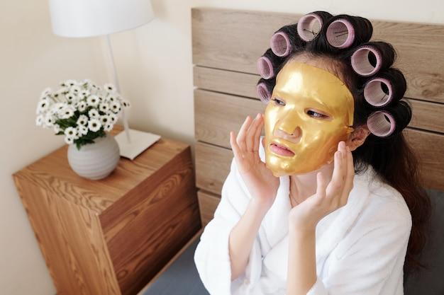 頭にヘアローラーを付けてベッドに座って、顔にシリコンシートマスクを適用する若い女性