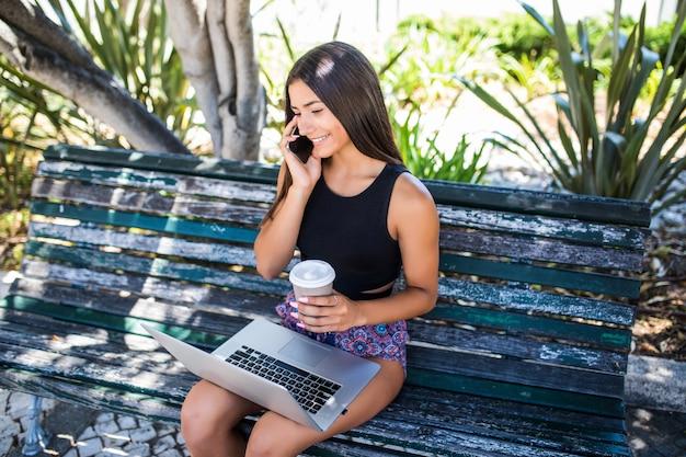 Молодая женщина, сидя на скамейке, разговаривает на смартфоне, работает на ноутбуке на открытом воздухе.