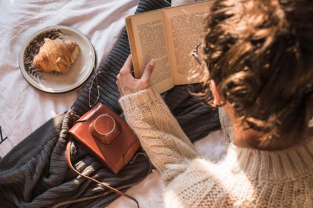 Молодая женщина, сидя на одеяло и чтение книги