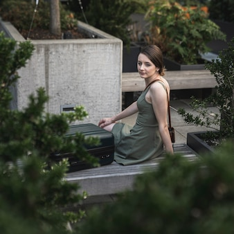 Молодая женщина сидит на цементном сиденье в городском парке