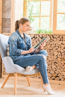 Young woman sitting on chair with listening music