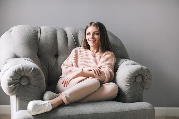 自宅で快適な椅子に座っている若い女性。