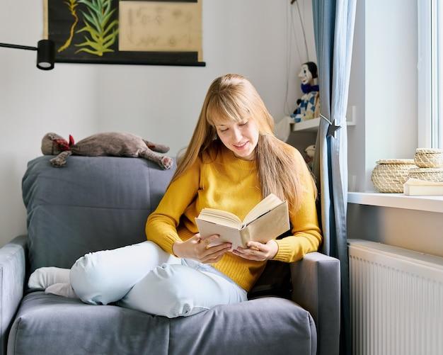 Молодая женщина сидит на диване и с энтузиазмом читает концепцию книги о социальной детоксикации