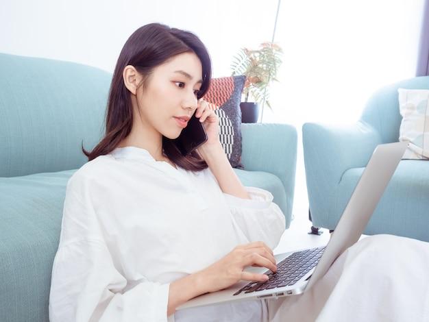 Молодая женщина, сидя на диване в гостиной дома одна, набрав в чате с помощью компьютера и разговаривая по телефону.