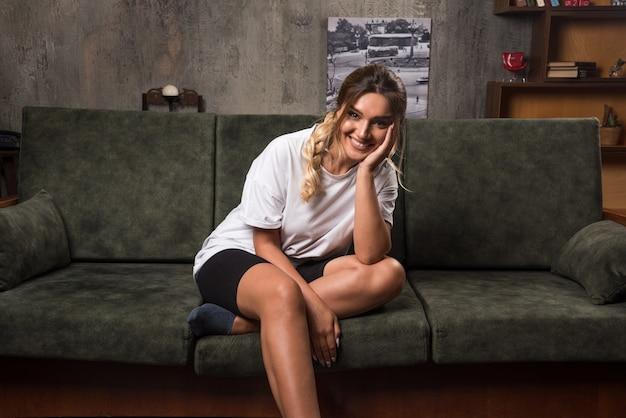 笑顔で正面を向いてソファに座っている若い女性。