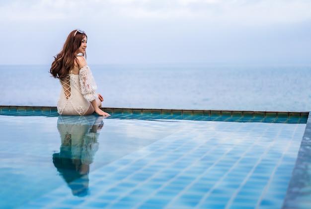 スイミングプールの端に座って海を見ている若い女性