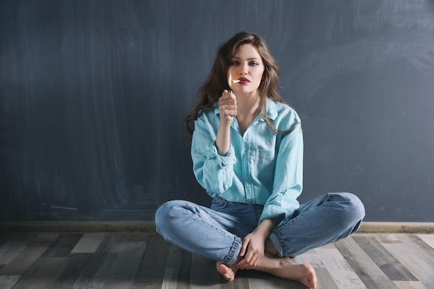 젊은여자가 바닥에 앉아 색 벽에 흡연