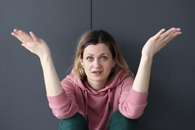 Молодая женщина сидит на полу и раскинула руки