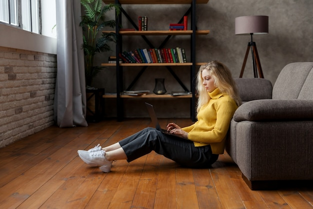 Молодая женщина сидит на полу дома и работает с ноутбуком.