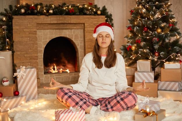 クリスマスイブに蓮華座で床に座っている若い女性は、目を閉じて自宅で瞑想し、落ち着いて真剣に、暖炉とクリスマスの木の近くで市松模様のズボン、シャツ、サンタの帽子をかぶっています。