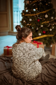 Young woman sitting on floor near Christmas tree