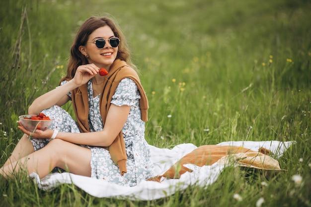草の上に座ってイチゴを食べる若い女性
