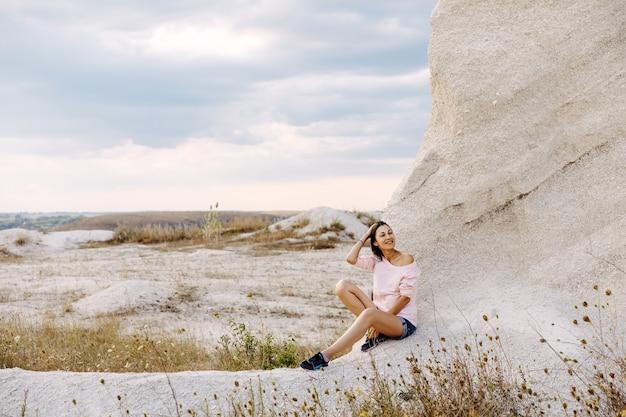 休暇を楽しんで、崖の地面に座っている若い女性。