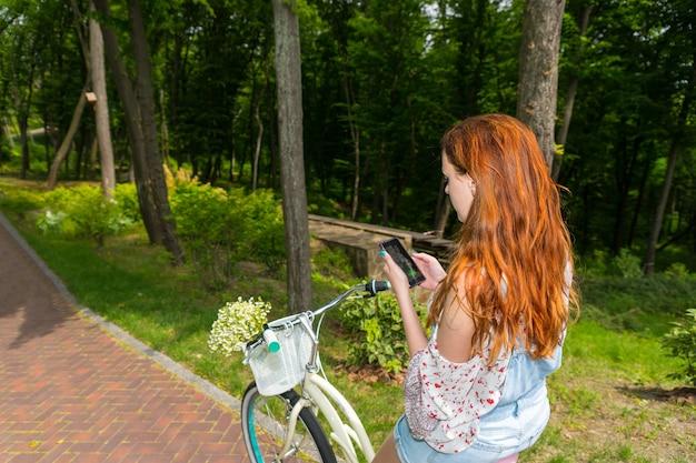 さまざまな木の背景を持つ公園で彼女の携帯電話を使用してバスケットに小さな白い花の花束を持って自転車に座っている若い女性