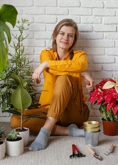 젊은여자가 그녀의 집 정원 바닥에 앉아