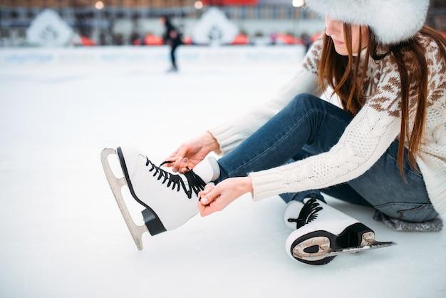 Молодая женщина сидит на льду и завязывает шнурки на коньках, катке. зимнее катание на коньках на свежем воздухе, активный отдых