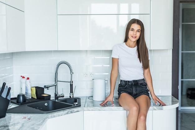 Молодая женщина, сидя на кухне счетчик дома