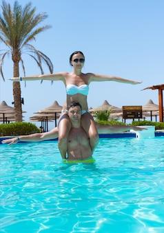화창한 여름날 호텔 수영장에서 아쿠아 피트니스를 하는 동안 남자의 목에 앉아 있는 젊은 여성