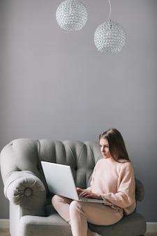 リラックスした雰囲気の中でラップトップに取り組んでいる自宅でモダンな椅子に座っている若い女性。