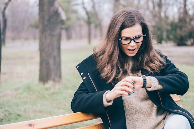 Молодая женщина сидит на скамейке в парке и проверяет время
