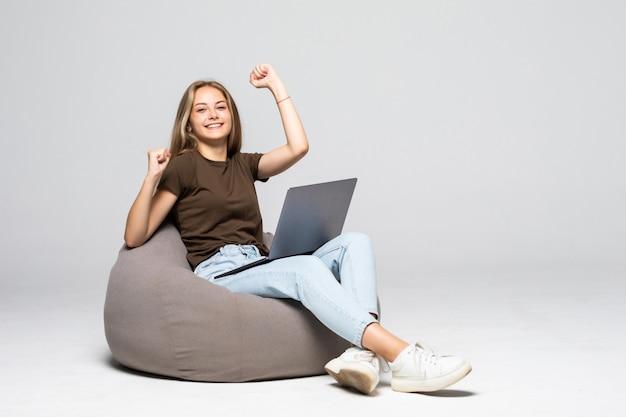 흰 벽에 고립 된 승리 제스처와 노트북과 pufff에 앉아 젊은 여자