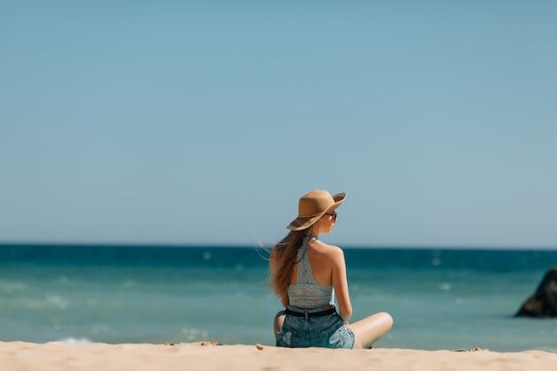 砂の上に座って海を探している若い女性。背面図