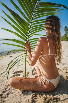 ヤシの木の葉の下の砂浜に座っている若い女性
