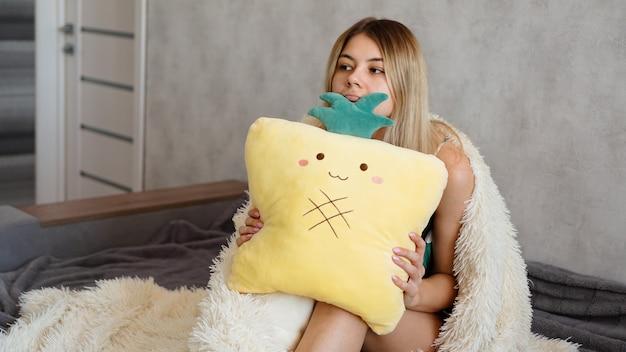 ソファに座って考えている若い女性。クッションを保持し、深刻または悲しそうに見える美しい少女