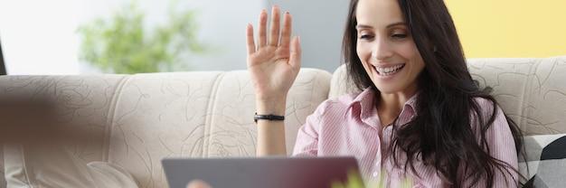 소파에 앉아서 노트북 화면에 손을 흔드는 젊은 여자. 소셜 네트워크 개념에 대한 원격 통신