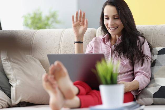 소파에 앉아서 노트북 화면을 흔들며 젊은 여자