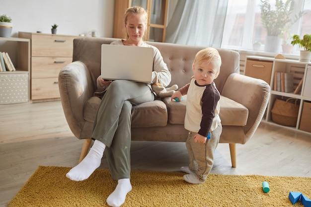 Молодая женщина сидит на диване и работает на ноутбуке, пока ребенок играет с игрушками в комнате