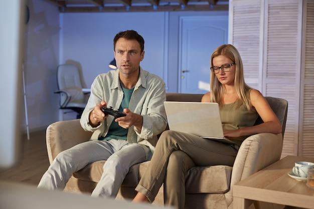 彼女のボーイフレンドが自宅で座っているコンピュータゲームで遊んでいる間、ソファに座ってラップトップで作業している若い女性
