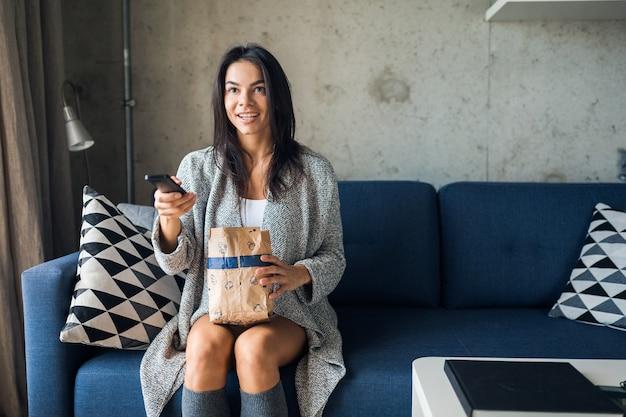 Молодая женщина, сидящая на диване дома, смотрит фильмы по телевизору, держит пульт, переключает каналы, ест попкорн, веселится, веселая, счастливая, забавная, удивленное выражение лица, эмоциональная