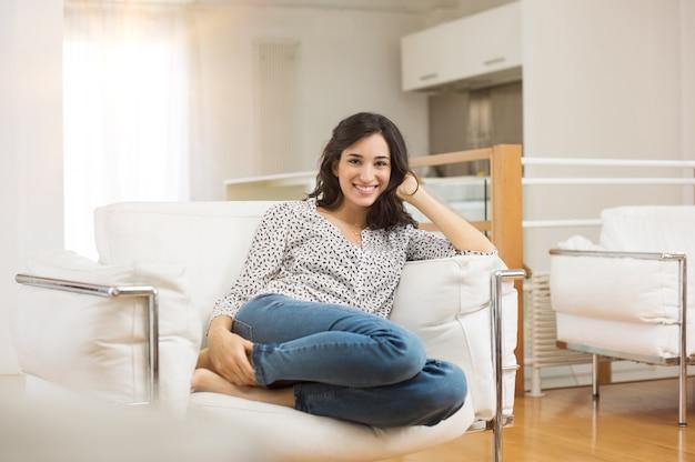 自宅のソファに座っている若い女性