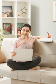 Молодая женщина, сидящая на диване за журнальным столиком, держит и использовала ноутбук, пишет книгу в гостиной